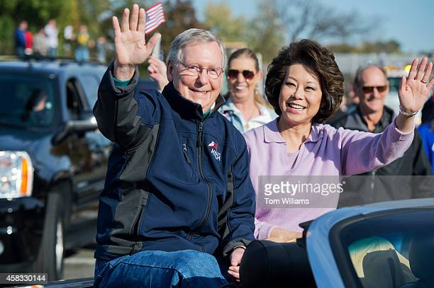Senate Minority Leader Mitch McConnell RKy and his wife Elaine Chao wave to the crowd during a veteran's parade in Madisonville Ky November 2 2014...