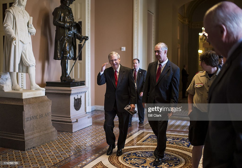 Senate Minority Leader Mitch McConnell, R-Ky., salutes Sen. Pat Leahy, D-Vt., as he makes his way to speak to the media in the Ohio Clock Corridor before the Senate Republicans' policy lunch on Tuesday, July 23, 2013. . Sen. Leahy was speaking to a group of Boy Scouts when the Minority Leader passed by.