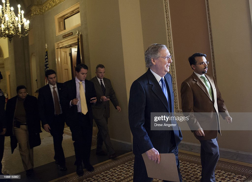 Senate Minority Leader Mitch McConnell (R-KY) walks with an aide toward the Senate Chamber on Capitol Hill December 30, 2012 in Washington, DC. The House and Senate are both in session today to deal with the looming 'fiscal cliff.' issue.