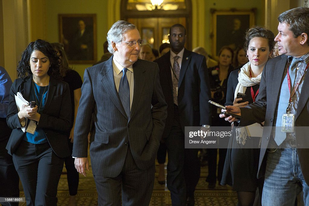 Senate Minority Leader Mitch McConnell (R-KY) walks with reporters on his way to a meeting with Republicans on Capitol Hill December 30, 2012 in Washington, DC. The House and Senate are both in session today to deal with the looming 'fiscal cliff.' issue.