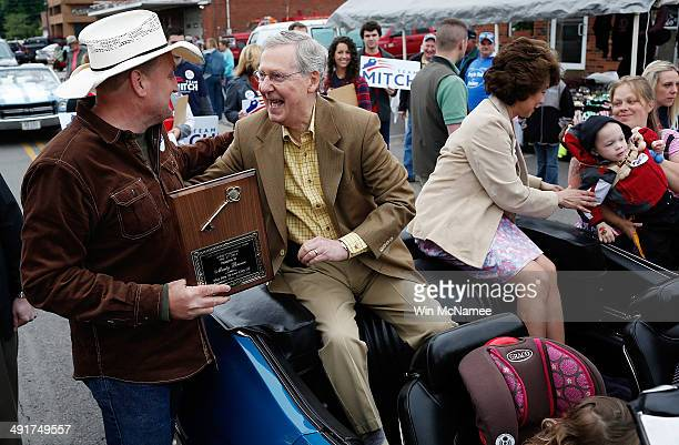 Senate Minority Leader Sen Mitch McConnell greets voters while riding in the Fountain Run BBQ Festival parade with his wife Elaine Chao while...