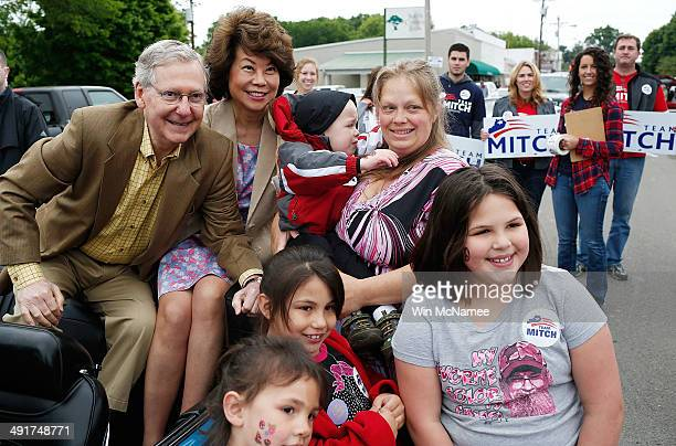 Senate Minority Leader Sen Mitch McConnell poses for a photo while riding in the Fountain Run BBQ Festival parade with his wife Elaine Chao while...