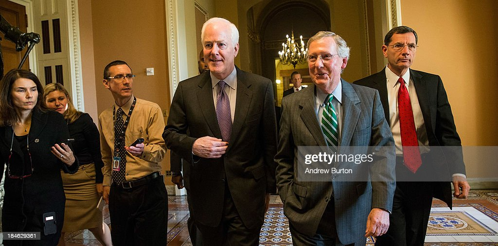 U.S. Senate Minority Whip Sen. <a gi-track='captionPersonalityLinkClicked' href=/galleries/search?phrase=John+Cornyn&family=editorial&specificpeople=154884 ng-click='$event.stopPropagation()'>John Cornyn</a> (R-TX), Senate Minority Leader <a gi-track='captionPersonalityLinkClicked' href=/galleries/search?phrase=Mitch+McConnell&family=editorial&specificpeople=217985 ng-click='$event.stopPropagation()'>Mitch McConnell</a> (R-KY), and Sen. John Barrasso (R-WY) walk from McConnell's office to the Senate Chamber on October 14, 2013 in Washington, DC. As Democratic and Republican leaders negotiate an end to the shutdown and a way to raise the debt limit, the White House postponed a planned Monday afternoon meeting with Boehner and other Congressional leaders. The government shutdown is currently in its 14th day.