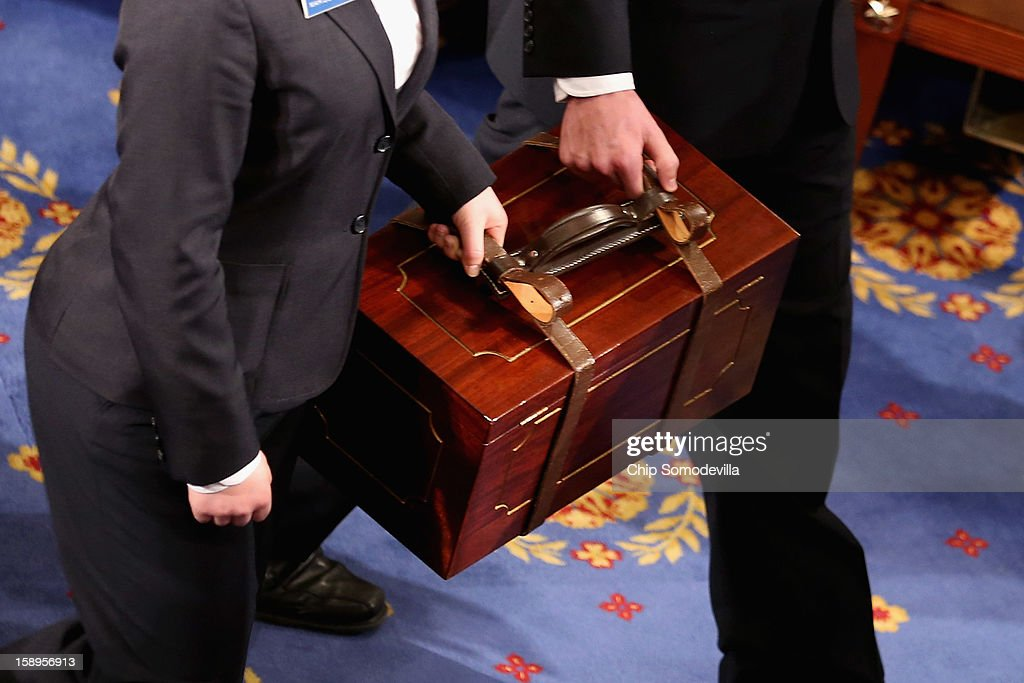 Senate pages carry bound wooden boxes containing the Electorial College votes from the 50 states into the House of Representatives chamber at the U.S. Capitol January 4, 2013 in Washington, DC. The votes were tallied during a joint session of the 113th Congress. President Barack Obama and Vice President Joe Biden received 332 votes to be reelected.
