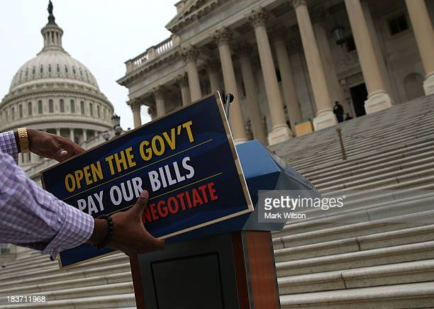 Senate staffer attaches a sign to a podium during a news conference on the government shutdown at the US Capitol October 9 2013 in Washington DC The...