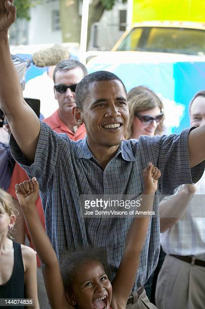 US Senator Barak Obama victorious after playing a game with his daughter while campaigning for President at Iowa State Fair in Des Moines Iowa August...