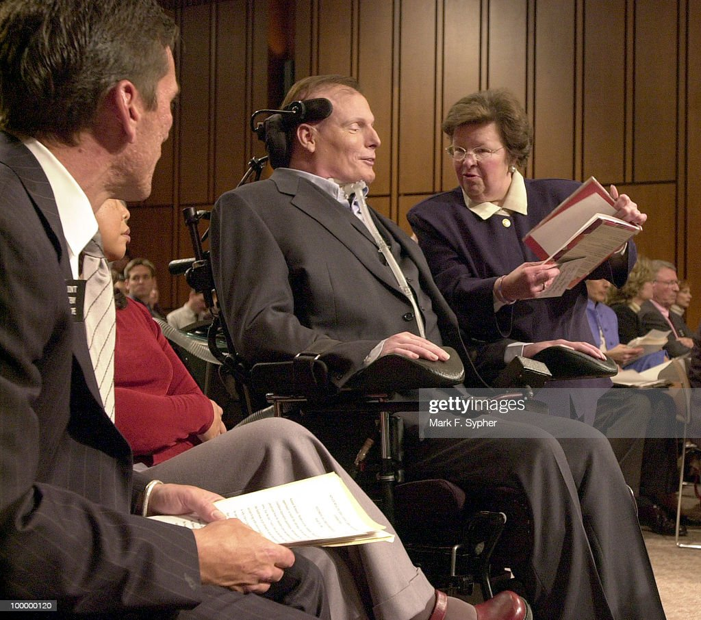 Senator Barbara A. Mikulski (D-MD) stops by to show Christopher Reeve a book before the full committee hearing on Tuesday which examined the dangers of cloning and the promise of regenerative medicine, in the Hart Building.