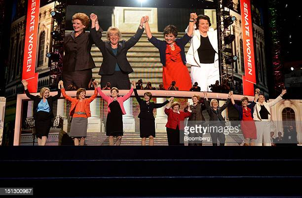 Senator Barbara Mikulski a Democrat from Maryland center raises hands with women of the Senate during day two of the Democratic National Convention...