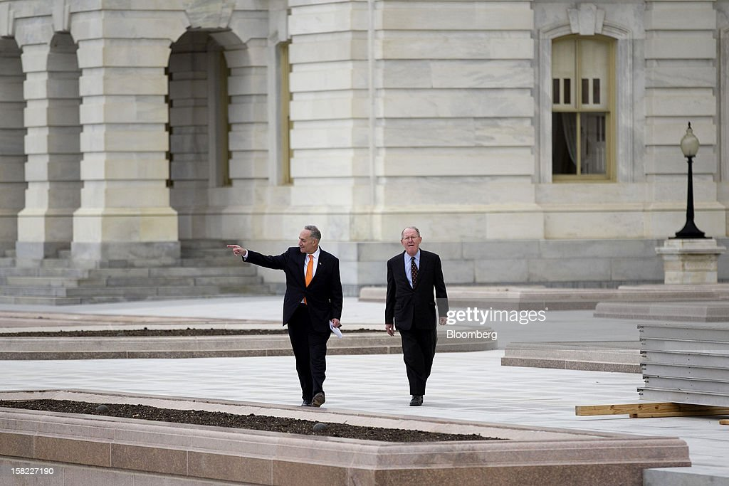 Senator Charles Schumer, a Democrat from New York, left, and Senator Lamar Alexander, a Republican from Tennessee, arrive to a news conference next to construction of the platform being built on the west front of the U.S. Capitol in preparation for the inauguration ceremony of U.S. President Barack Obama in Washington, D.C., U.S., on Tuesday, Dec. 11, 2012. The presidential inauguration ceremony will take place on Jan. 21, 2013. Photographer: Andrew Harrer/Bloomberg via Getty Images
