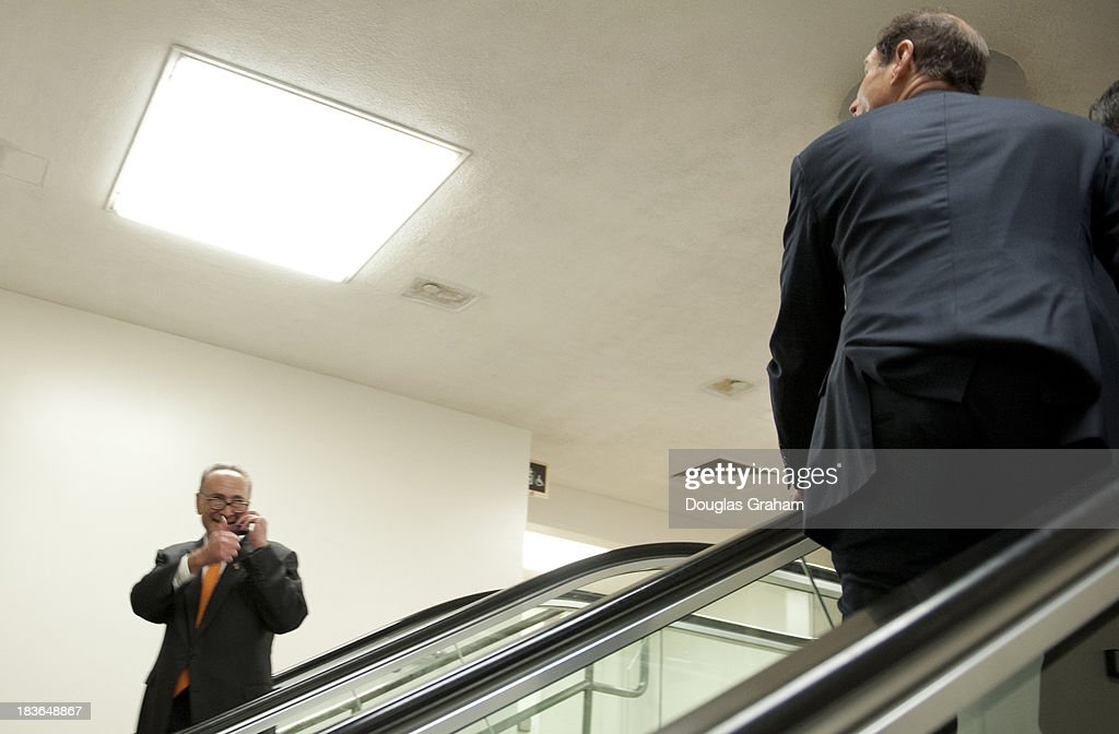 Senator Charles Schumer, D-NY., gives Senator Ron Wyden, D-OR., the thumbs up in the senate subway during the policy luncheons in the U.S. Capitol on October 8, 2013.