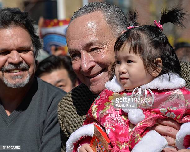 S Senator Chuck Schumer holds a young ChineseAmerican girl wearing a traditional costume Members of New York City's ChineseAmerican community...
