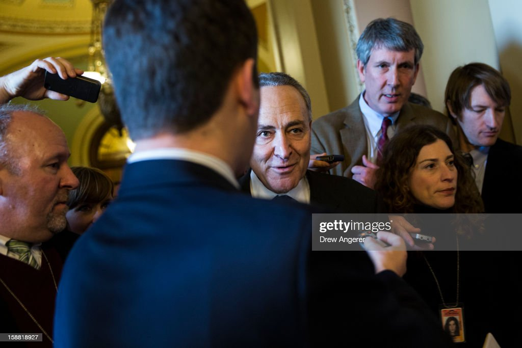 Senator Chuck Schumer (D-NY) (C) talks with reporters on his way to a meeting with Senate Democrats on Capitol Hill December 30, 2012 in Washington, DC. The House and Senate are both in session today to deal with the looming 'fiscal cliff.' issue.