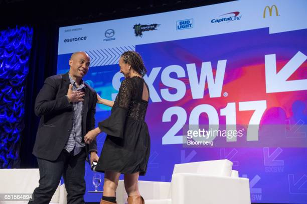 Senator Cory Booker a Democrat from New Jersey left reacts to Malika Saada Saar senior counsel on civil and human rights for Google Inc at the...
