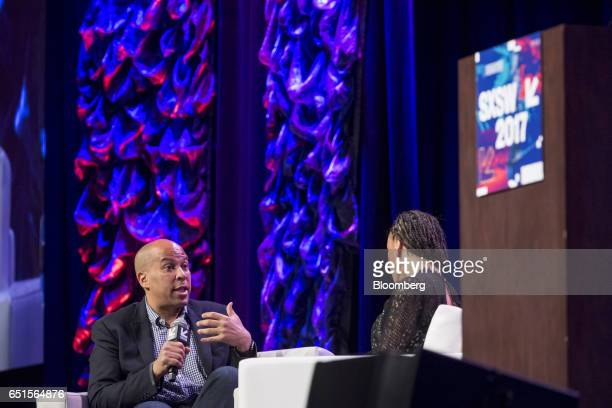 Senator Cory Booker a Democrat from New Jersey left speaks as Malika Saada Saar senior counsel on civil and human rights for Google Inc listens...
