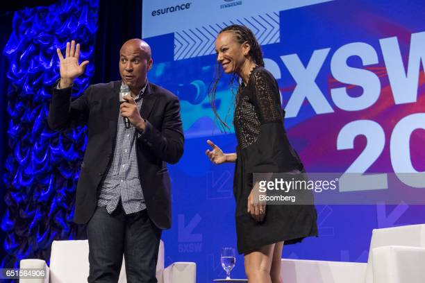 Senator Cory Booker a Democrat from New Jersey left waves to the crowd while on stage with Malika Saada Saar senior counsel on civil and human rights...