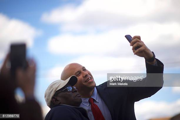 Senator Cory Booker takes a photo with a supporter as he arrives for a Breaking Down Barriers Town Hall for Democratic Presidential candidate former...