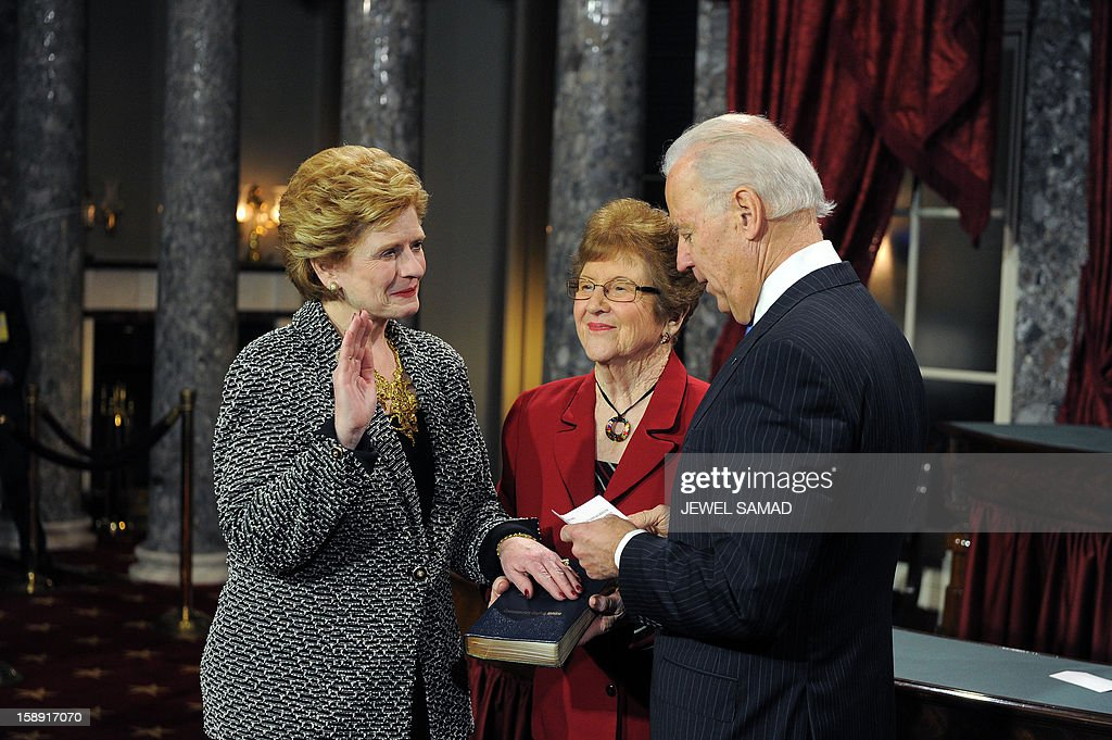 US Senator Debbie Stabenow, D-MI, (L) participates in a reenacted swearing-in with his son Robert Menendez and daughter Alicia Jacobsen Menendez and US Vice President Joe Biden in the Old Senate Chamber at the U.S. Capitol January 3, 2013 in Washington, DC. The 113th US Congress, featuring dozens of new faces in the House and Senate, convened Thursday fresh from the year-end 'fiscal cliff' fiasco, as lawmakers cast a wary eye towards the tough budget battles ahead. AFP PHOTO/Jewel Samad