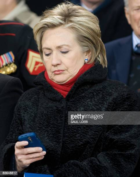 US Senator Democrat Hillary Clinton of New York looks at her Blackberry during the Veterans Day rededication of the Intrepid Sea Air Space Museum in...