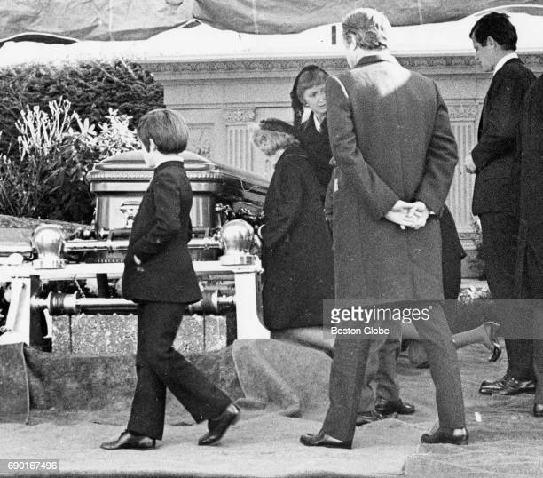 Senator Edward M Kennedy and brotherinlaw Sargent Shriver family and friends at father's Joseph P Kennedy Sr grave site following funeral service at...