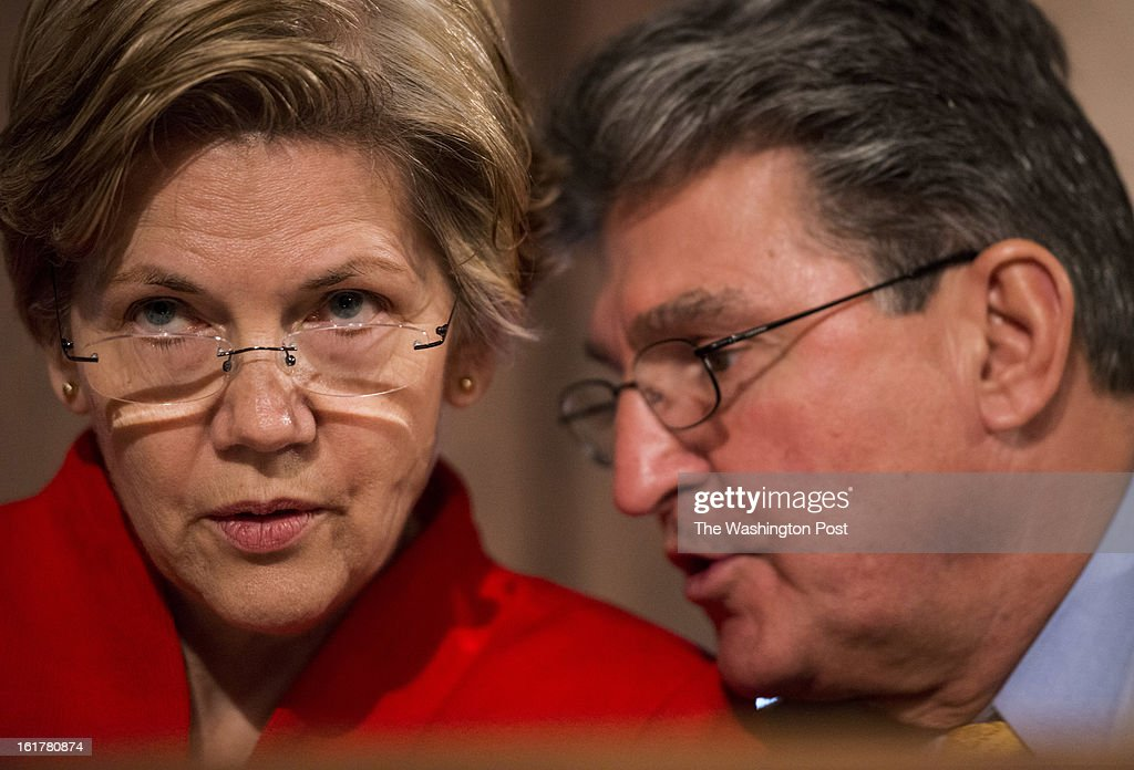 Senator Elizabeth Warren during her first hearing as a US Senator, speaks with Senator Joe Manchin (D-WV) quietly at the Senate Banking Committee on Capitol Hill Thursday, February 14, 2013.