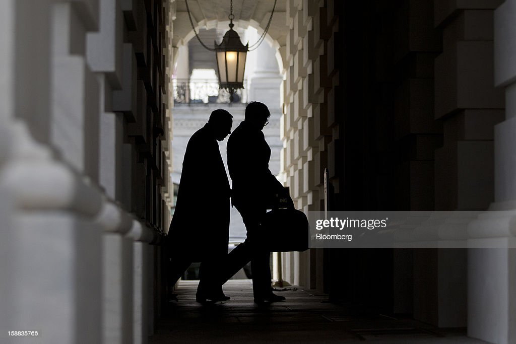 Senator Harry Reid, a Democrat from Nevada, left, walks into the U.S. Capitol in Washington, D.C., U.S., on Monday, Dec. 31, 2012. U.S. lawmakers hurtled toward a midnight deadline to avert hundreds of billions of dollars in tax increases and spending cuts, struggling to extract the country from a fiscal trap they created. Photographer: Andrew Harrer/Bloomberg via Getty Images