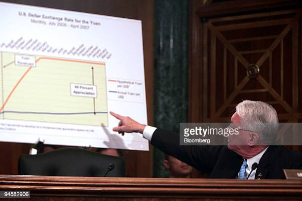 Senator Jim Bunning points to a chart on the US Dollar Exchange rate for the Yuan as he makes a statement at a hearing of the US Senate Committee on...