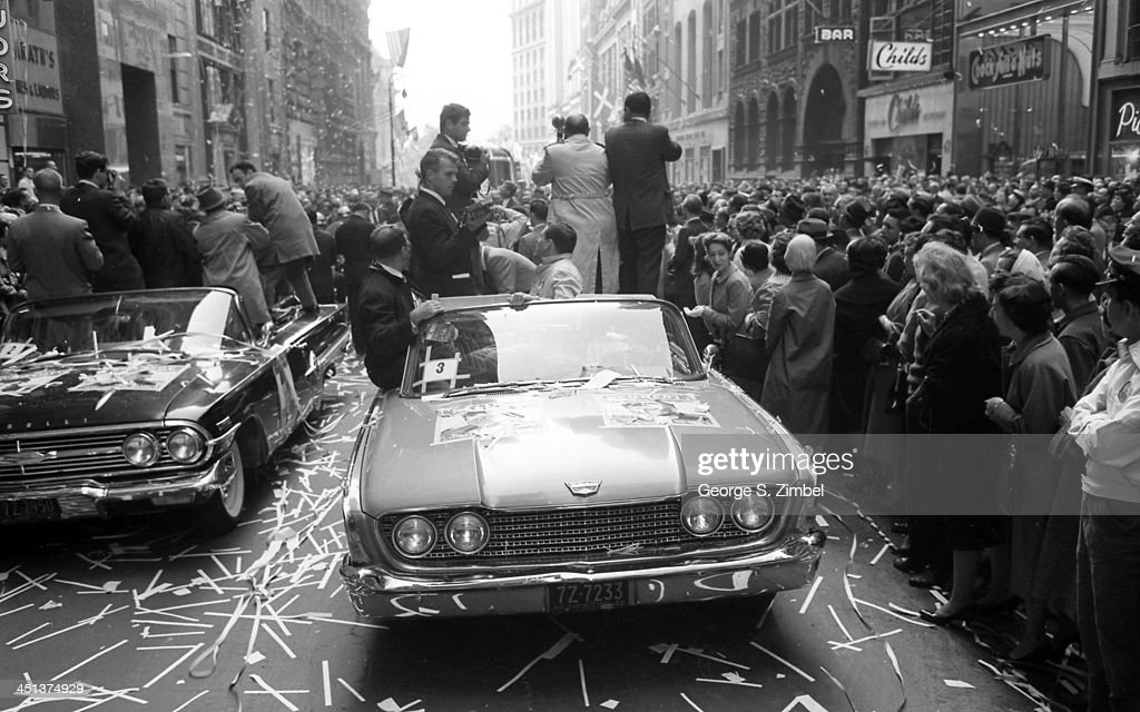 Senator John F Kennedy barely visible while looking up and riding in a trailing car is the center of attention for photographers in cars and crowds...