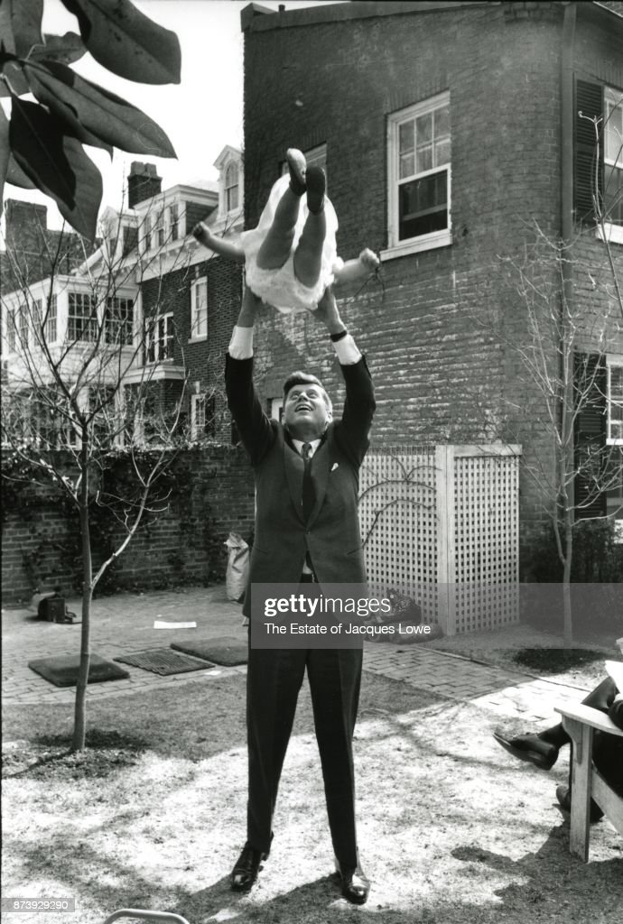 """And here's JFK and daughter Caroline playing in the yard of their townhouse in the Georgetown neighborhood of DC. Earlier this year Caroline said of her father """"I have thought about him and missed him every day of my life."""