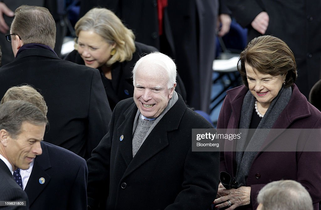 Senator John McCain, a Republican from Arizona, center, and Senator Dianne Feinstein, a Democrat from California, right, arrive during the U.S. presidential inauguration in Washington, D.C., U.S., on Monday, Jan. 21, 2013. As he enters his second term President Barack Obama has shed the aura of a hopeful consensus builder determined to break partisan gridlock and adopted a more confrontational stance with Republicans. Photographer: Joshua Roberts/Bloomberg via Getty Images