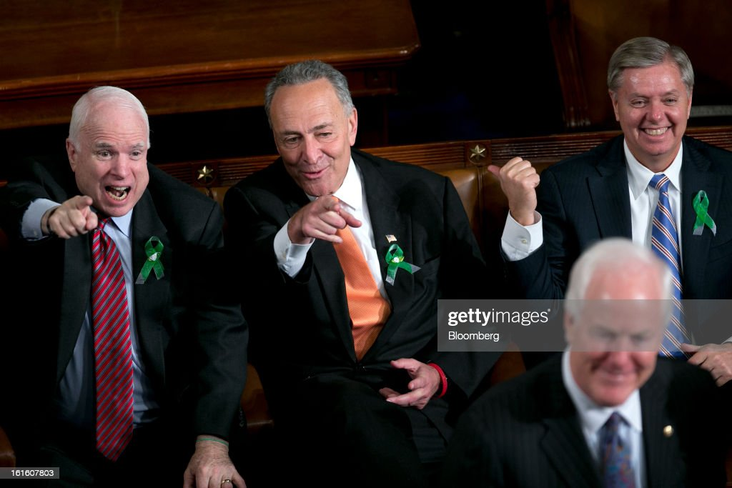 Senator John McCain, a Republican from Arizona, left, Senator Charles Schumer, a Democrat from New York, second left, and Senator Lindsey Graham, a Republican from South Carolina, right, gesture before U.S. President Barack Obama, unseen, delivers the State of the Union address to a joint session of Congress at the Capitol in Washington, D.C., U.S., on Tuesday, Feb. 12, 2013. Obama called for raising the federal minimum wage to $9 an hour and warned he'll use executive powers to get his way on issues from climate change to manufacturing if Congress doesn't act, laying out an assertive second-term agenda sure to provoke Republicans. Photographer: Andrew Harrer/Bloomberg via Getty Images
