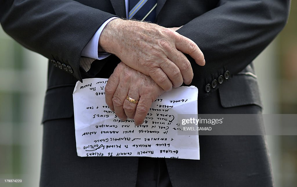 US Senator John McCain holds is notes as he and his colleague Senator Lindsey Graham, R-SC, answer a questions following a meeting with US President Barack Obama at the White House in Washington, DC, on September 2, 2013. McCain said Monday that Congress's failure to authorize military action in Syria would be 'catastrophic' because it would undermine US credibility. AFP Photo/Jewel Samad