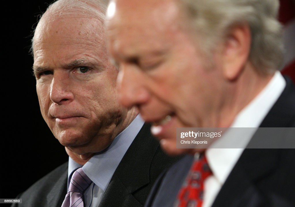 US Senator John McCain (R-AZ) listens to Senator Joe lieberman (I-CT) speak during a news briefing June 25, 2009 on Capitol Hill in Washington, DC. McCain has proposed legislation to assist the people of Iran in promoting democracy. He said he would like to increase US-backed radio broadcasts into Iran.