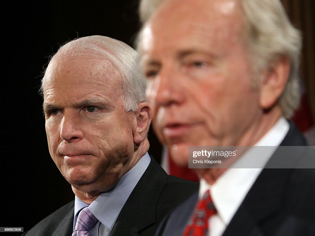 U.S. Senator John McCain (R-AZ) listens to Senator Joe lieberman (I-CT) speak during a news briefing June 25, 2009 on Capitol Hill in Washington, DC. McCain has proposed legislation to assist the people of Iran in promoting democracy. He said he would like to increase US-backed radio broadcasts into Iran.