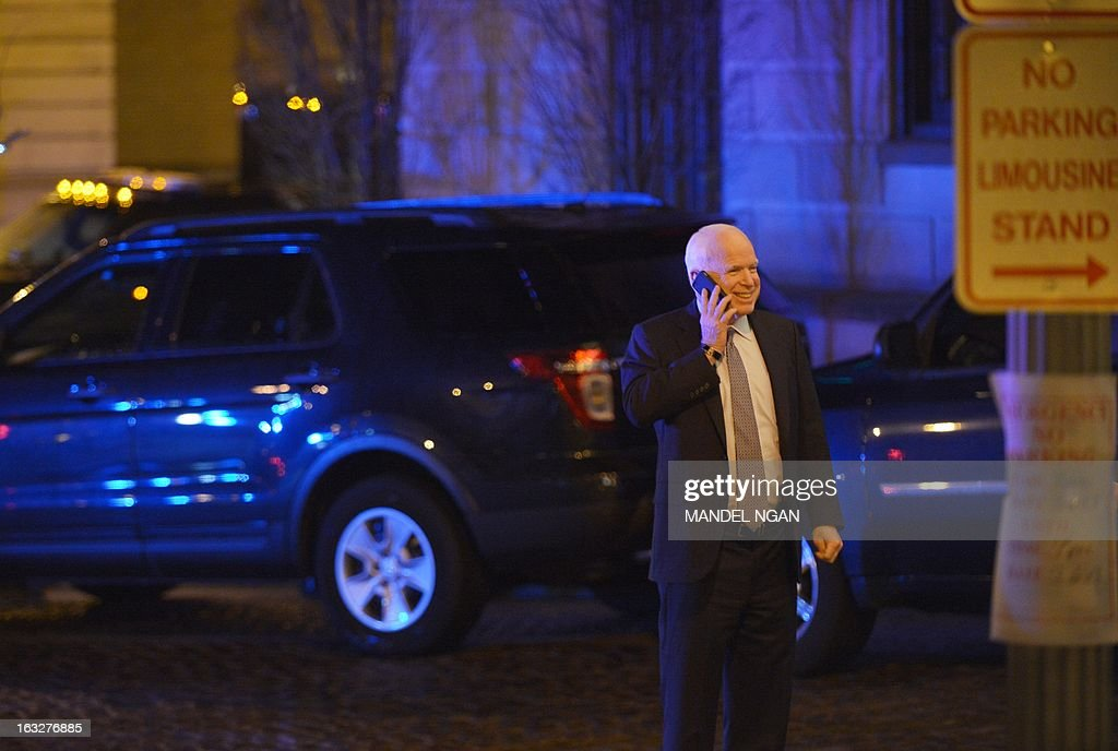 Senator John McCain, R-AZ, speaks on the phone outside of the Jefferson Hotel following a dinner with US President Barack Obama and a group of fellow Republican senators on March 6, 2013 in Washington, DC. US President Obama met Republican senators for a rare dinner March 6, 2013, as he sought to end an ugly budget stalemate that is clouding the early days of his second term. AFP PHOTO/Mandel NGAN