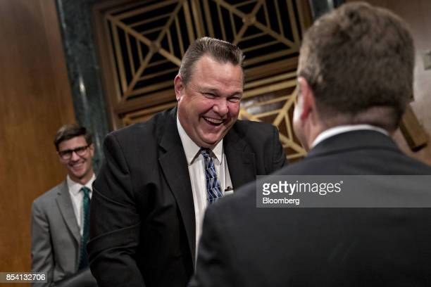Senator Jon Tester a Democrat from Montana laughs while talking to Jay Clayton chairman of the US Securities and Exchange Commission right before a...