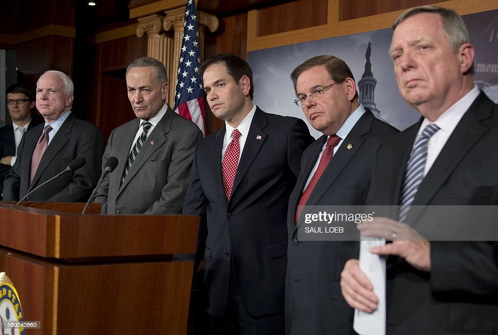 Senator Marco Rubio (C), Republican from Florida, listens to a question alongside (L-R) Senator John McCain (R-AZ), Senator Chuck Schumer (D-NY), Senator Robert Menendez (D-NJ) and US Senator Dick Durbin (D-IL) during a press conference on an agreement for principles on comprehensive immigration reform framework at the US Capitol in Washington, DC, on January 28, 2013. AFP PHOTO / Saul LOEB
