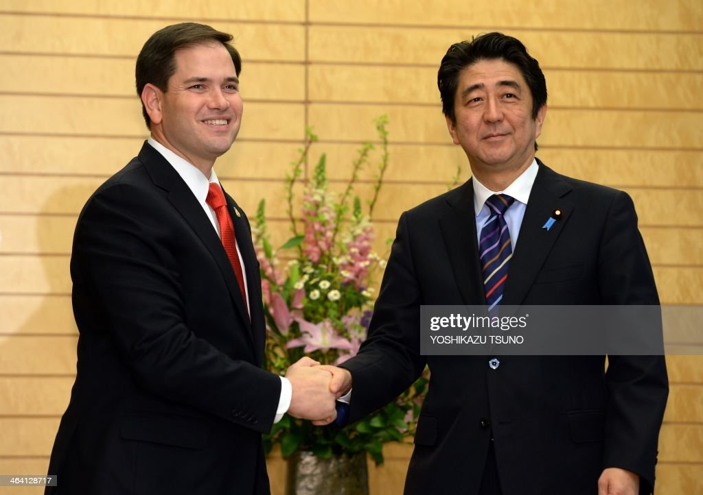 US Senator Marco Rubio (L) shakes hands with Japanese Prime Minister Shinzo Abe (R) prior to their talks at Abe's office in Tokyo on January 21, 2014. Rubio, a member of the US Senate Foreign Relations Committee is in Japan for talks with Japanese officials. AFP PHOTO / POOL / Yoshikazu TSUNO