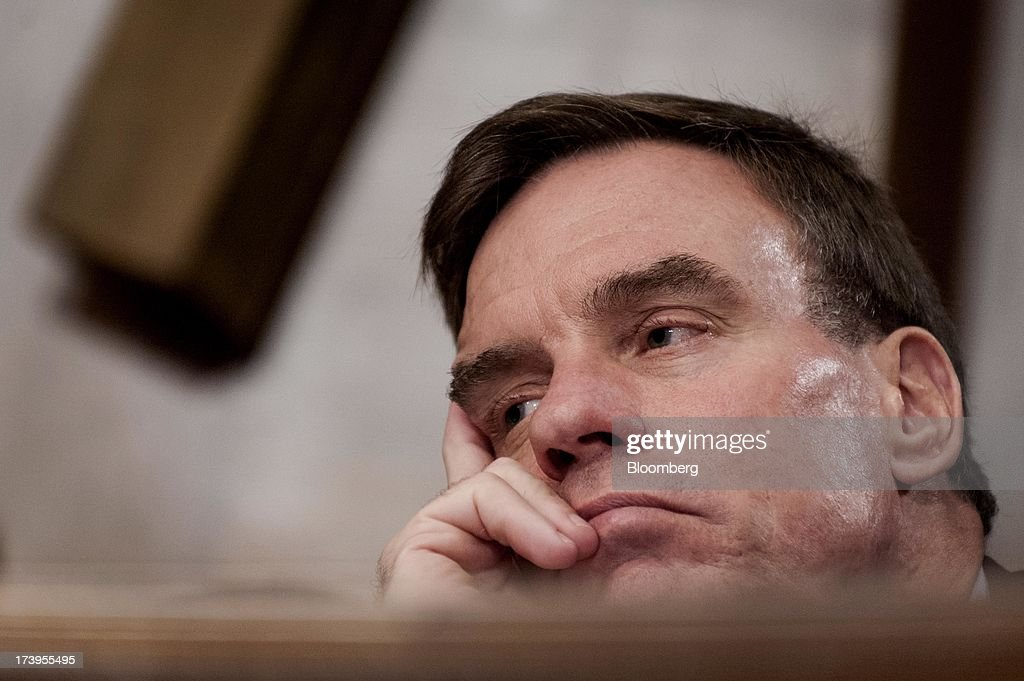 Senator <a gi-track='captionPersonalityLinkClicked' href=/galleries/search?phrase=Mark+Warner&family=editorial&specificpeople=2251151 ng-click='$event.stopPropagation()'>Mark Warner</a>, a Democrat from Virginia, listens as Ben S. Bernanke, chairman of the U.S. Federal Reserve, not seen, delivers his semi-annual monetary policy report to the Senate Banking, Housing, and Urban Affairs Committee in Washington, D.C., U.S., on Thursday, July 18, 2013. Bernanke said one reason for the recent rise in long-term interest rates is the unwinding of leveraged and 'excessively risky' investing. Photographer: Pete Marovich/Bloomberg via Getty Images