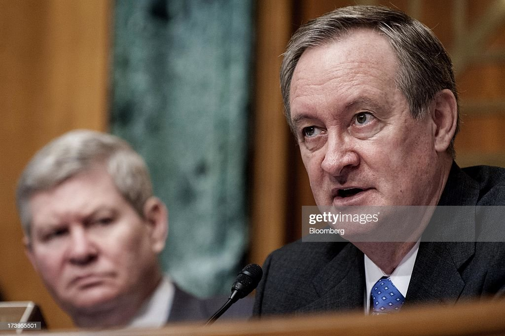Senator Mike Crapo, a Republican from Idaho, right, questions Ben S. Bernanke, chairman of the U.S. Federal Reserve, not seen, during his semi-annual monetary policy report to the Senate Banking, Housing, and Urban Affairs Committee as Chairman Tim Johnson, a Democrat from South Dakota, listens in Washington, D.C., U.S., on Thursday, July 18, 2013. Bernanke said one reason for the recent rise in long-term interest rates is the unwinding of leveraged and 'excessively risky' investing. Photographer: Pete Marovich/Bloomberg via Getty Images