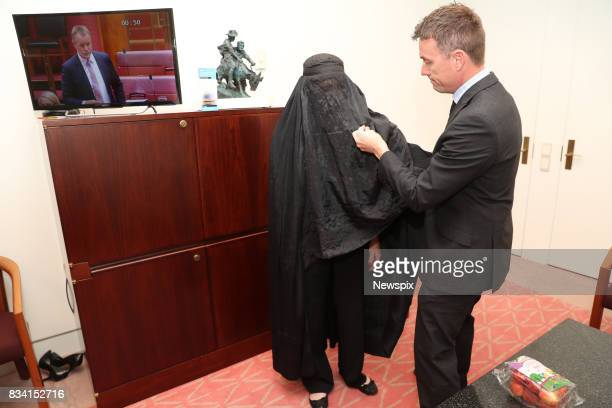 CANBERRA ACT Senator Pauline Hanson puts on a burqa with the help of James Ashby ahead of her appearance in Parliament in Canberra Australian Capital...