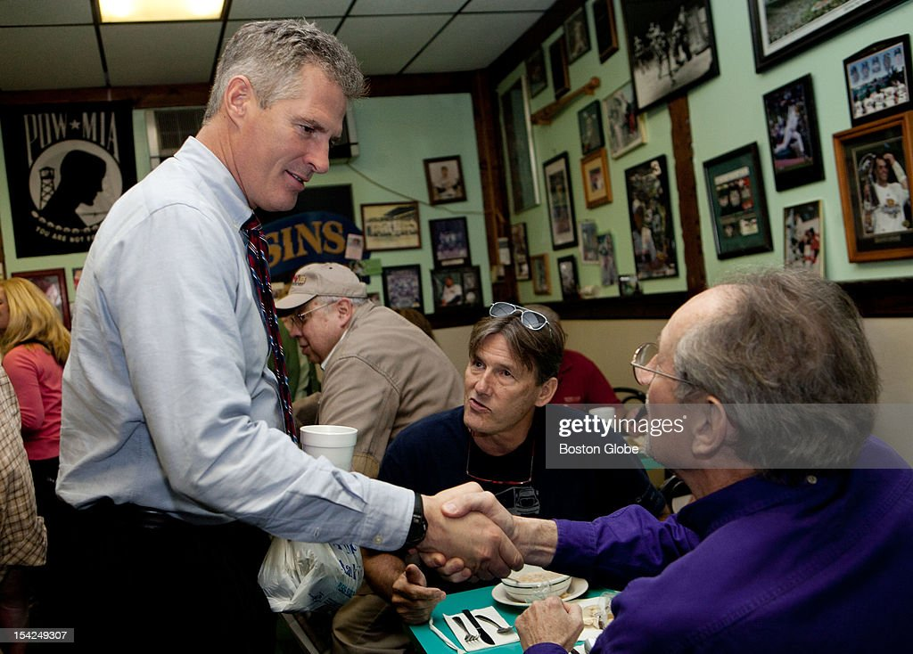Senator Scott Brown greets diners Terry Hanley, right, and Dennis Lovelace, center, at Cousin's Restaurant in Woburn, Mass., on October 15, 2012.
