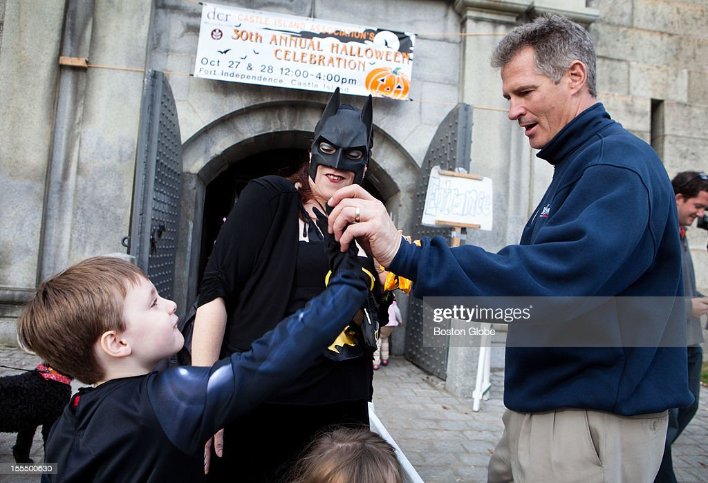 Senator Scott Brown high-fives Curtis Burke, 6, as his mother Susan Burke looks on, in front of the Magical Halloween Castle on Castle Island on October 27, 2012.