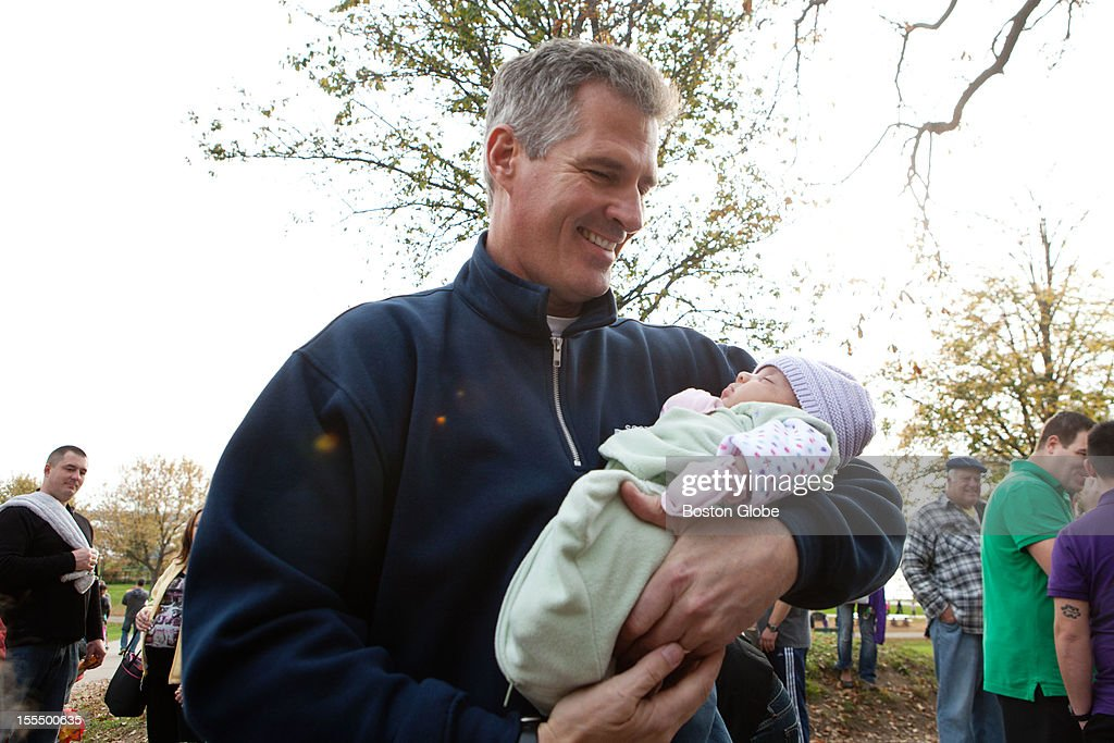 Senator Scott Brown holds one month old baby Samra Brito while greeting people in front of the Magical Halloween Castle on Castle Island on October 27, 2012.
