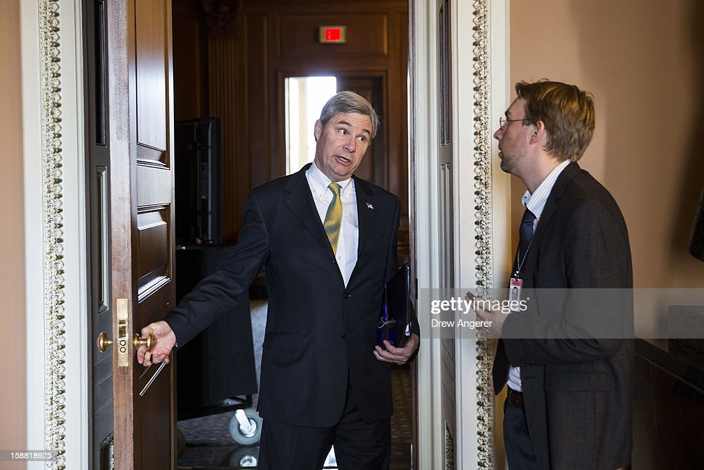 Senator <a gi-track='captionPersonalityLinkClicked' href=/galleries/search?phrase=Sheldon+Whitehouse&family=editorial&specificpeople=599442 ng-click='$event.stopPropagation()'>Sheldon Whitehouse</a> (D-RI) speaks with a reporter on his way into a meeting with Senate Democrats on Capitol Hill December 30, 2012 in Washington, DC. The House and Senate are both in session today to deal with the looming 'fiscal cliff.' issue.