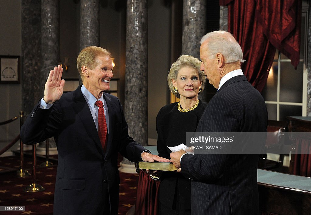 US Senator Tom Carper, D-DE, (L) participates in a reenacted swearing-in with US Vice President Joe Biden in the Old Senate Chamber at the U.S. Capitol January 3, 2013 in Washington, DC. The 113th US Congress, featuring dozens of new faces in the House and Senate, convened Thursday fresh from the year-end 'fiscal cliff' fiasco, as lawmakers cast a wary eye towards the tough budget battles ahead. AFP PHOTO/Jewel Samad