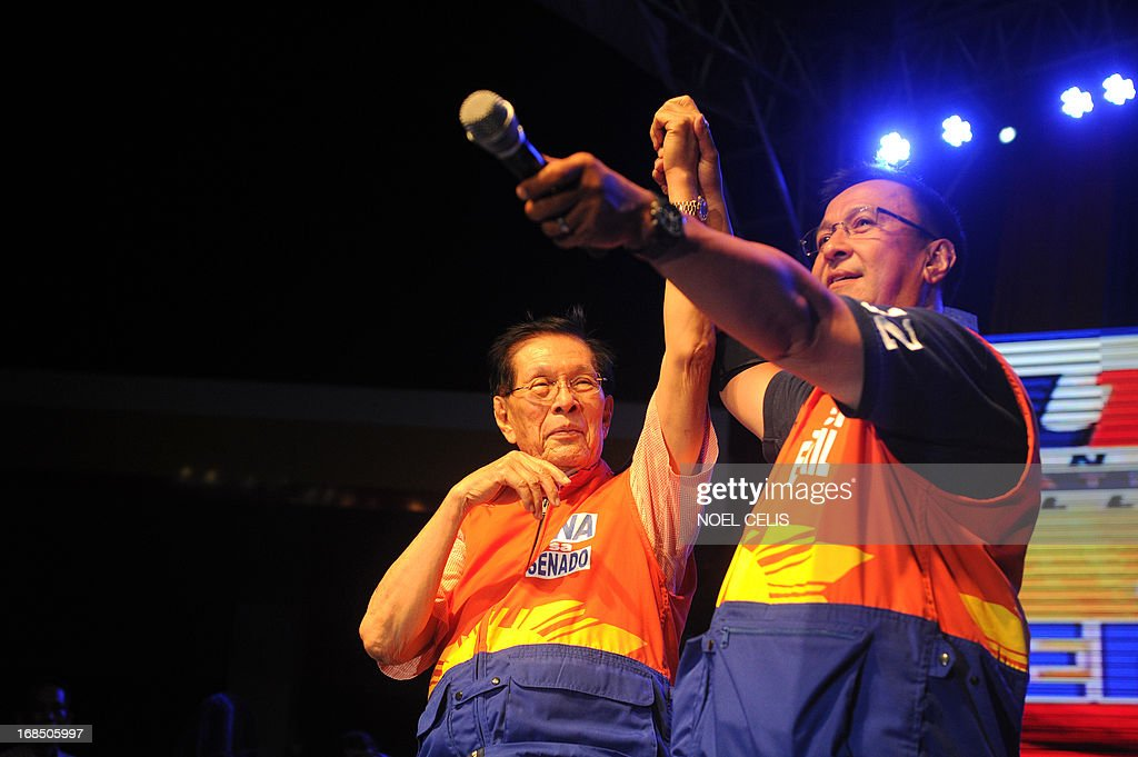 Senatorial candidate Juan Ponce Enrile JR (R) raises the hands of his father, Senate President Juan Ponce Enrile (L) during a political rally in Manila on May 10, 2013. Estrada is running for Mayor in Manila. Political dynasties have long been a feature of politics in the Philippines but analysts say that clan rule is becoming more entrenched, with a remarkably few number of families dominating elected posts at national and local levels. Another political neophyte polling well is Nancy Binay, daughter of Vice President Jejomar Binay. Once a human rights lawyer, the patriarch is building his own dynasty with two other children already holding top political posts. AFP PHOTO/Noel Celis