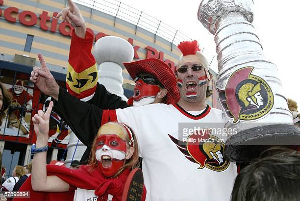 Senators fans Bryanna Brian and Steve Lester pump up the crowd at the Party Plaza outside of Scotiabank Place before the Ottawa Senators take on the...