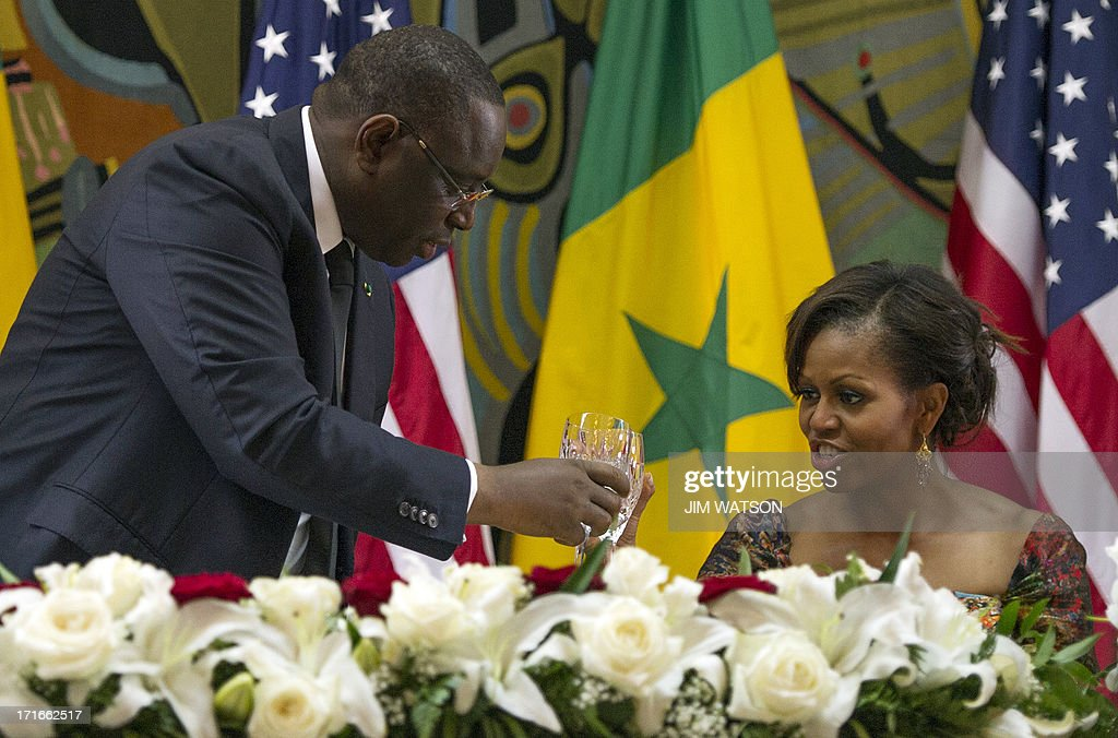 Senegal President Macky Sall (L) toasts with US First Lady Michelle Obama during an official dinner at the Presidential Palace in Dakar on June 27, 2013. Obama hit out at discrimination against gays in Africa and hailed the continent's 'amazing' progress and potential today on the first leg of a three-country tour.