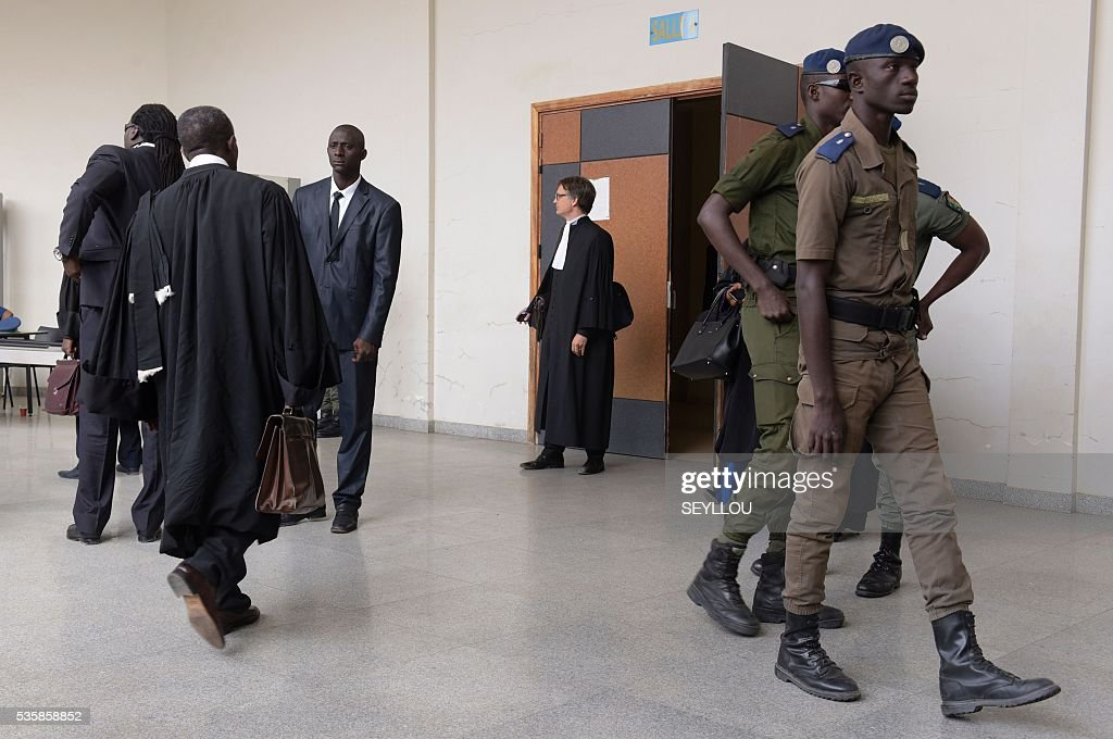 Senegal security members and lawyers walk in the hall of the Dakar Courthouse ahead of the sentencing of former Chadian dictator Hissene Habre on May 30, 2016 in Dakar. Former Chadian dictator Hissene Habre was found guilty of crimes against humanity and sentenced to life in prison by a special court in Senegal on May 30, 2016. The case, at the Extraordinary African Chambers (CAE) - a special tribunal set up by the African Union under a deal with Senegal - is the first time a country has prosecuted a former leader of another nation for rights abuses. / AFP / SEYLLOU