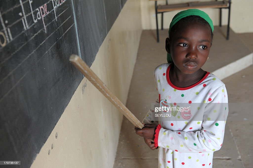 Senegalese 7-year-old pupil Ndeye Fatou Ndiaye attends a lesson in her classroom, on 10 June 2013, at the Franco-Arab school of Diagnel, 14km south of Kaolack, central Senegal.